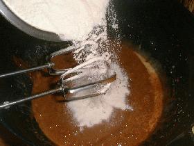 Faire fondre le chocolat au micro-ondes. Dans un plat, mélanger le sucre, le sucre vanillé, les œufs et le beurre fondu puis ajouter la farine et le chocolat. Après avoir égouté l'ananas mélanger celui-ci coupé en dés avec le reste de la pâte