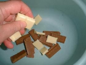 dans un saladier, casser le chocolat pralinoise et le blanc en morceaux. faire fondre au bain marie
