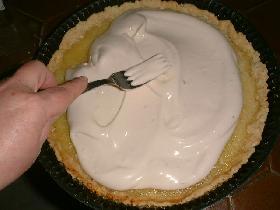 retirer la tarte du four et étaler la meringue à la fourchette en la tournant  pour donner un effet de volume. enfourner à nouveau