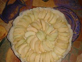 couper les pommes en lamelles épaisses, ranger les sur la pâte en les faisant légèrement se chevaucher et enfourner pendant 15mn